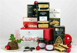 SMALL RED CHRISTMAS GIFT BOX WITH GOLD RIBBON CONTAINING CRISPS, PRESERVES, BISCUITS, MINCEMEAT PIE, CHRISTMAS PUDDING AND CHOCOLATES. gOLD AND RED THEMED HAMPER