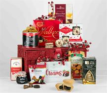 A OVAL WILLOW SHOPPING BASKET FILLED WITH CHRISTMAS PRODUCTS THAT INCLUDE BISCUITS CHOCOLATES NUETS SAVOURY BITES, CHRISTMAS PUDDING