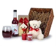 A brown banana lead basket with a white teddybear, chocolates gift wrapped 2 yankee candles and luscombe raspberry presse