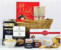 A wicker swing handle shopping basket with a selection of cheese biscuits, chocolates, sweet biscuits, cake slices and preserves