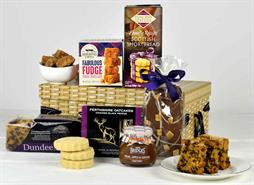 A gift boxc with a wicker basket print and black ribbon fiulled with scottish shortbread, dundee cake, fudge, oatcakes, chocolates and chutney