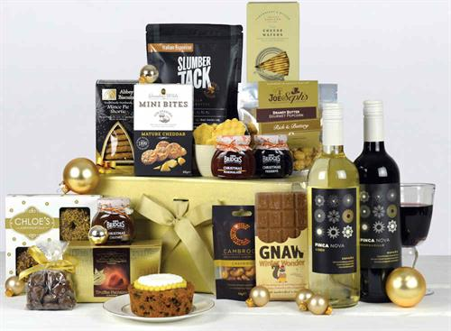 Luxury christmas hamper in a gold box with two bottles of wine, christmas cake, biscuits, chocolate, nuts, preserve and other popular snacks