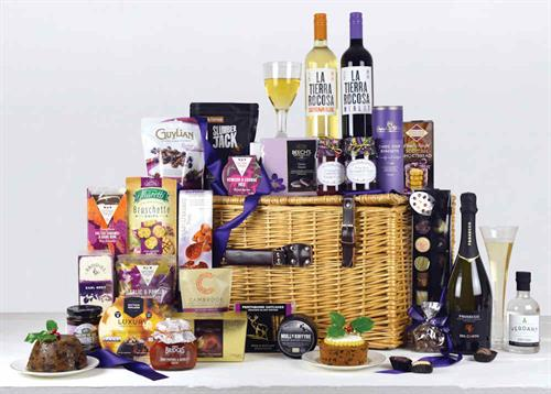 Traditional willow basket with leather straps and handle filled with champagne, wines, port, savoury snacks, preserves,m cheese, chakes, biscuits, chocolates. Purple and green colour theme