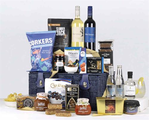 a blue twisted rope basket filled with 2 bottles of wine gin and tonics and a well balanced range of high quality products