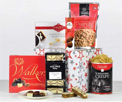 Non alcoholic hamper filed with savoury and sweet snacks presented in a red and grey star design carton